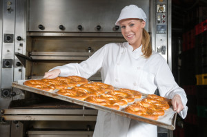 Baker with baking plate full of pastry in bakery